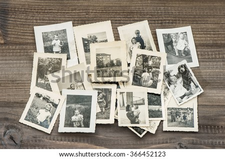 Old family photos on wooden table. Vintage pictures  - stock photo