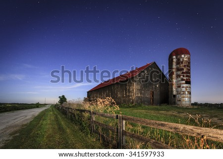 Old farm barn and a country road in moonlight - stock photo