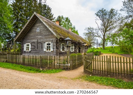 Old farm house in Lithuania with a fence - stock photo