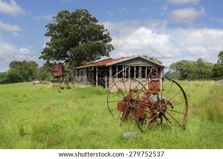 Old farm shed or barn, with a rusty water tank and cart wheels lie in overgrown grass in Benandarah NSW Australia - stock photo