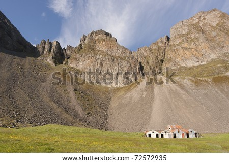 Old farm under a mountain and blue sky - stock photo