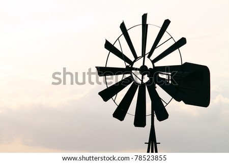 Old Farm Windmill for Pumping Water with Spinning Blades at Sunset in New Mexico, USA - stock photo
