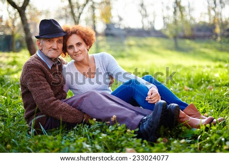 Old farmer and his daughter sitting in the grass, resting - stock photo