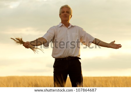 Old farmer with a bouquet of wheat in the sunlight. outdoor shot - stock photo