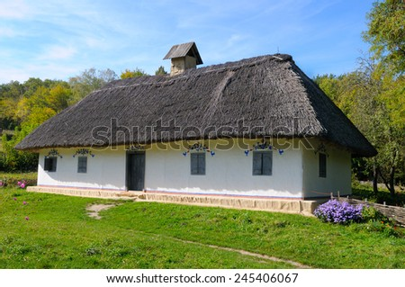 old farmhouse with a thatched roof - stock photo