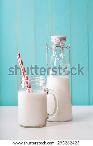 Old fashion milk jar and mason jar with big red paper striped straws on pastel blue background - stock photo