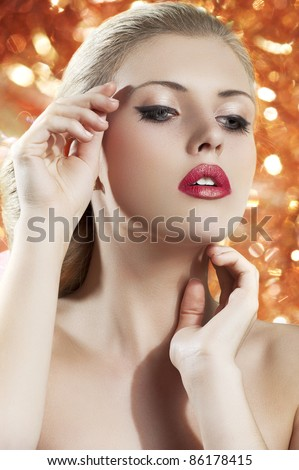 old fashion portrait of a young beautiful blond woman with hair style and deep red yellow lips on black background - stock photo