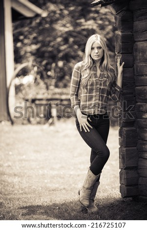 Old fashion portrait of a young lady posing next to an old timber cabin and barn area - stock photo