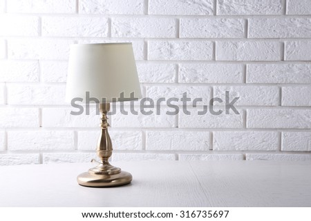 Old fashion table lamp on table on brick wall background - stock photo