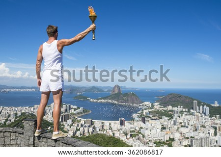 Old-fashioned athlete in classic vintage white sports uniform standing holding sport torch at city skyline overlook in Rio de Janeiro Brazil - stock photo