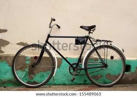 Old fashioned bicycle near rural pale yellow stucco wall - stock photo