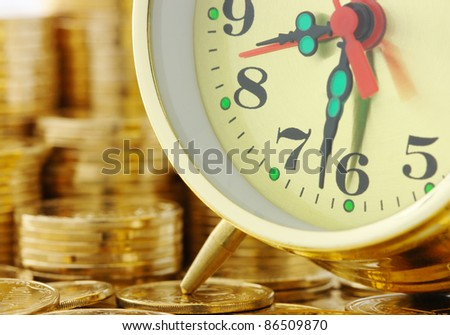 Old-fashioned clock dial on golden coins background, time is money concept - stock photo