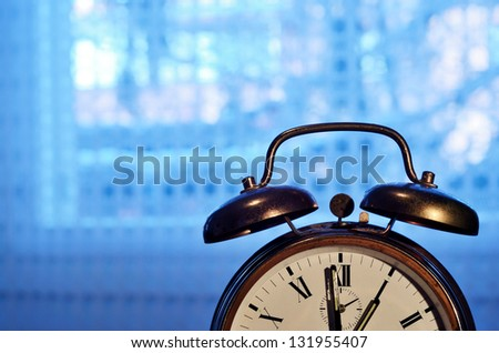 old-fashioned copper alarm clock  against blue window - stock photo