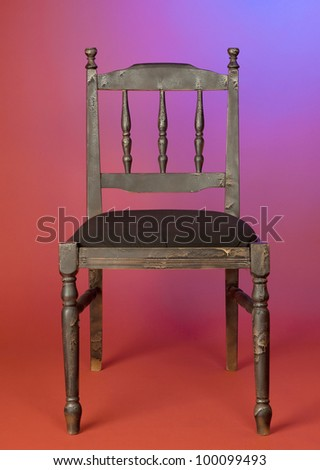 old-fashioned dark wood chair against red wall - stock photo
