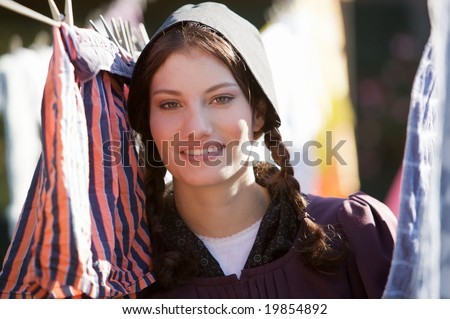 Old fashioned farmgirl hanging the laundry out - stock photo