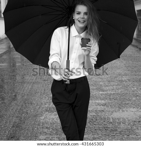 Old-fashioned girl under umbrella. Dressed in black pants, white shirt. Walking down the street in the rain and holding in hand paper coffee cup - stock photo
