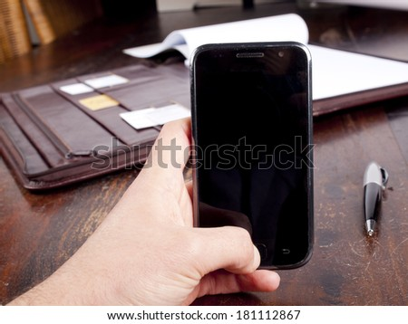 Old fashioned leather folder with blank paper and a modern smartphone - stock photo