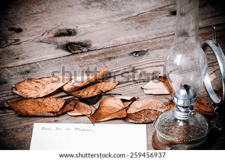 Old fashioned letter with a lamp and leafs - retro style, wooden background - stock photo