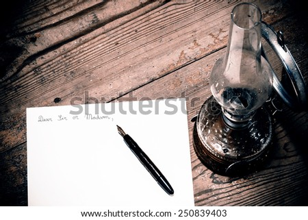 Old fashioned letter with a pen and lamp - retro picture possible use as postcard - stock photo