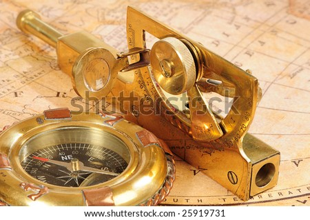 old-fashioned navigation devices on a background an old map - stock photo