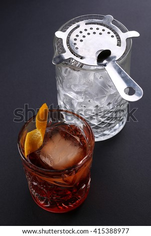 Old fashioned Negroni cocktail near glass with ice on the black background - stock photo