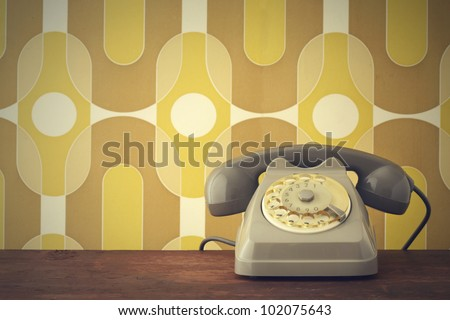Old-fashioned phone on vintage background - stock photo