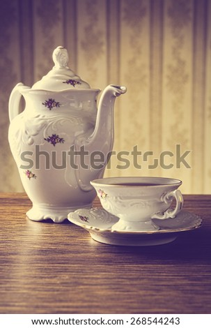 Old-fashioned porcelain jug with a cup of tea with old-fashioned wallpaper background - stock photo