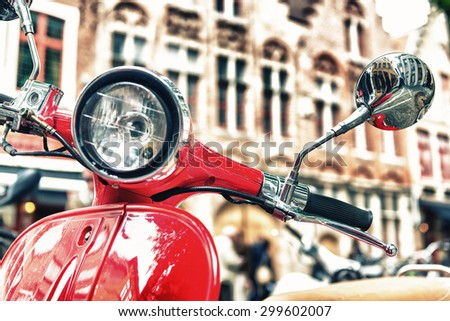 Old fashioned red motorbike parked in city center. - stock photo