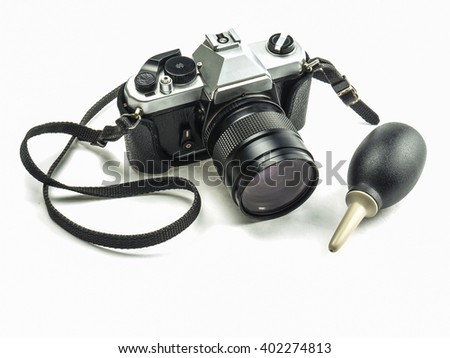 Old fashioned single lens reflex camera with rubber blower pump cleaner isolated over white background  - stock photo