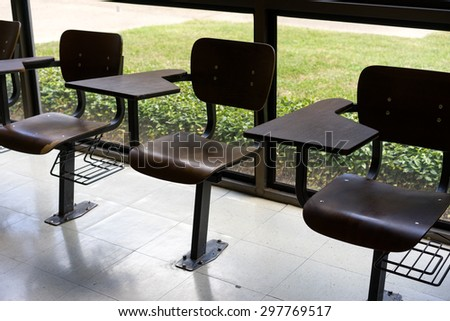 Old fashioned tablet-arm desk chairs in a classroom near a large window.  - stock photo