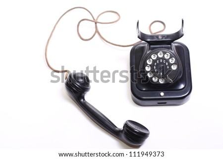 Old-fashioned telephone on the white backing - stock photo