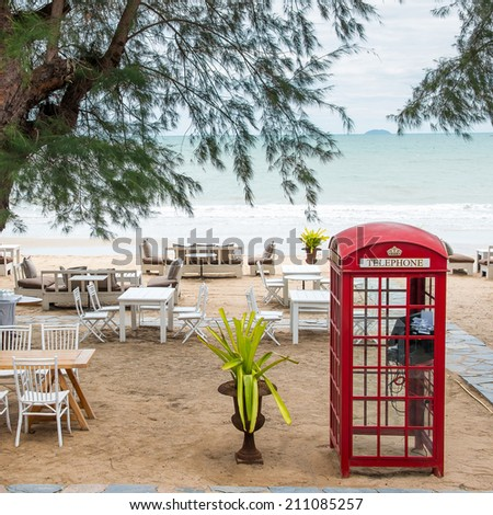 Old-fashioned traditional red public telephone booth on the beach - stock photo