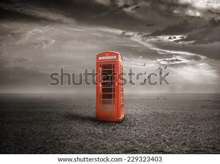 Old-fashioned traditional red telephone booth on deserted field - stock photo
