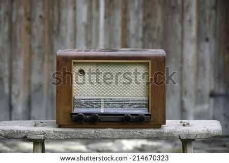 Old-fashioned vintage radio on a wooden bench - stock photo