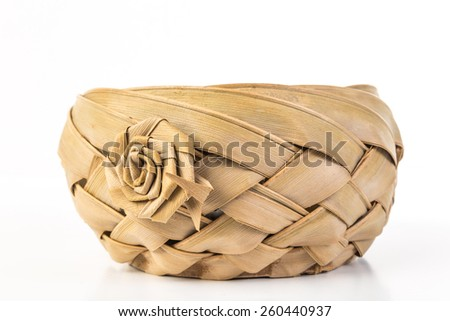 Old fashioned wicker basket weaved using thick bark straps with crafted flower.  White background with copy space. - stock photo