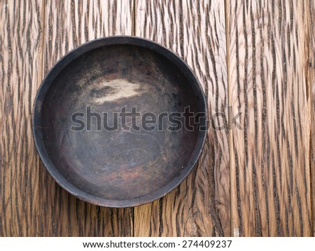 Old-fashioned wooden bowl on wooden table. - stock photo