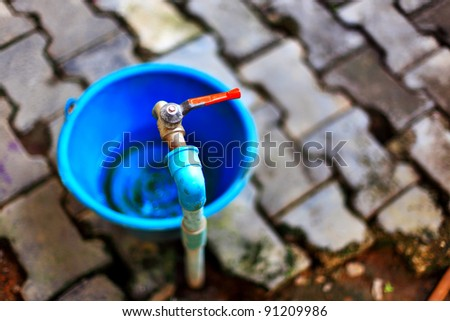 Old faucet with a blue bow. - stock photo