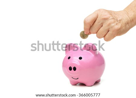 old female hand putting a golden coin into a pink piggy bank - saving for retirement concept - stock photo