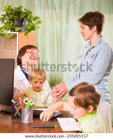 Old female pediatrician doctor examining children  - stock photo