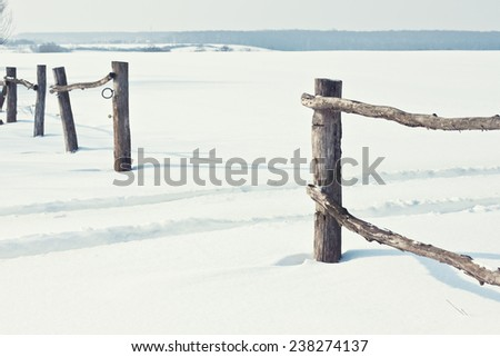 Old fence in snow on a sunny day - stock photo