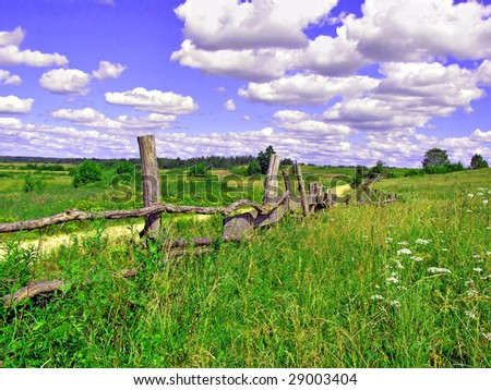 old fence on field near roads - stock photo