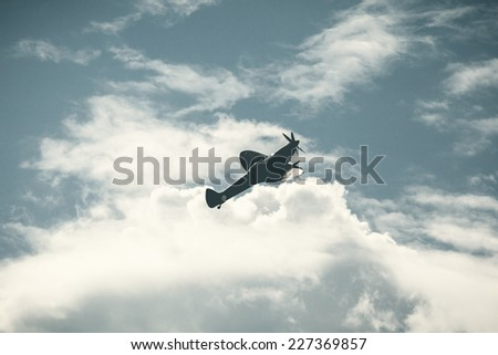 Old fighter plane on bright cloudy sky - stock photo