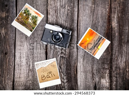 Old film camera and polaroid photos with Bali tropical beaches on the wooden background - stock photo