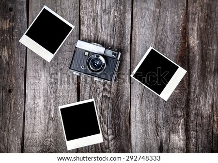 Old film camera and polaroid photos with space for pictures on the wooden background - stock photo