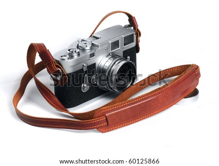 Old film camera with leather strap over white background - stock photo