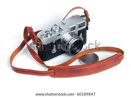 Old film camera with lens and leather strap over white background - stock photo