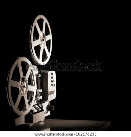Old film projector on a black backgroun - stock photo