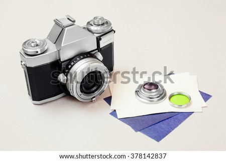 old film slr camera and filter - stock photo