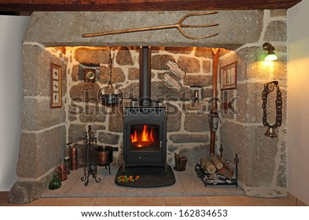 old fireplace made of stone and iron stove - stock photo