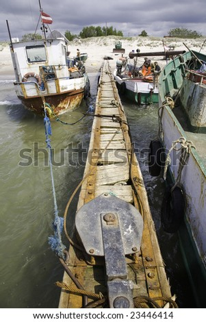 Old fisherman boats by jetty - stock photo